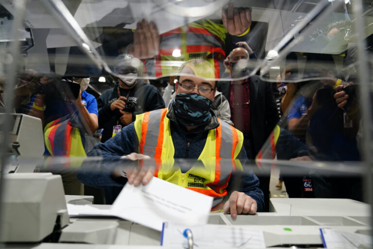John Hansberry, with the Philadelphia City Commissioners office, demonstrates an extraction machine at the city's mail-in ballot sorting and counting center in preparation for the 2020 General Election in the United States, Monday, Oct. 26, 2020, in Philadelphia. (AP Photo/Matt Slocum)