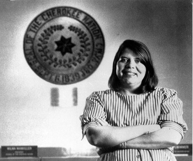 Black and white photography of Wilma Mankiller in front of the tribal emblem at the Cherokee Nation