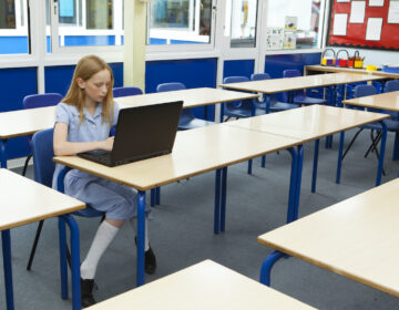 A student uses a laptop in an empty classroom.