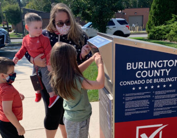 Nicole Flaherty, top, stands with her kids as her 7-year old daughter Madelyn places the ballot in the box in the Burlington County ballot box