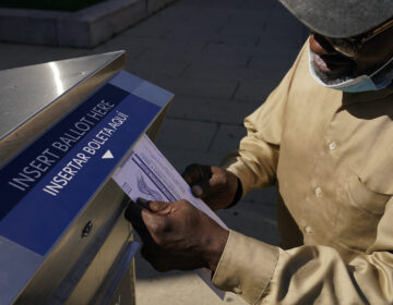 Robert Reed deposits his ballot in an election drop box in Newark, N.J.
