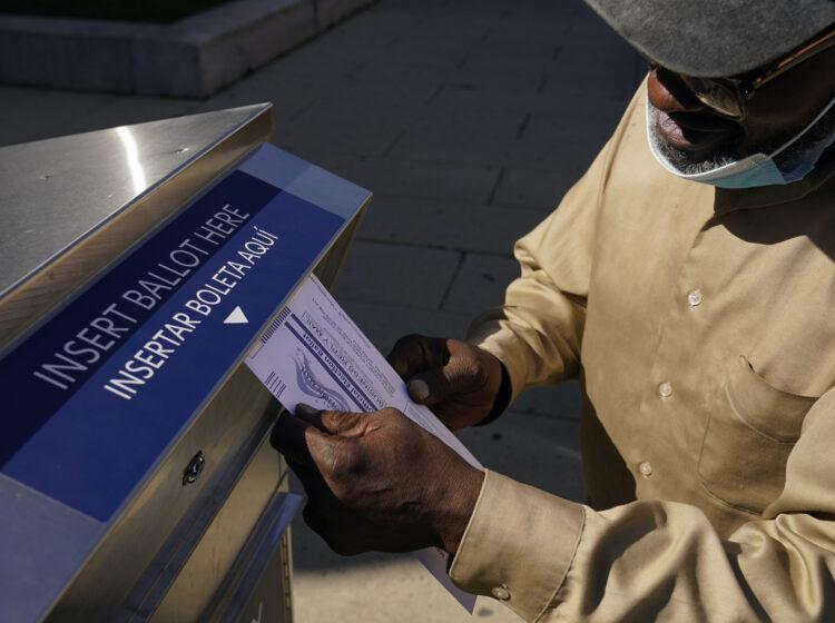 Robert Reed deposits his ballot in an election drop box in Newark, N.J.