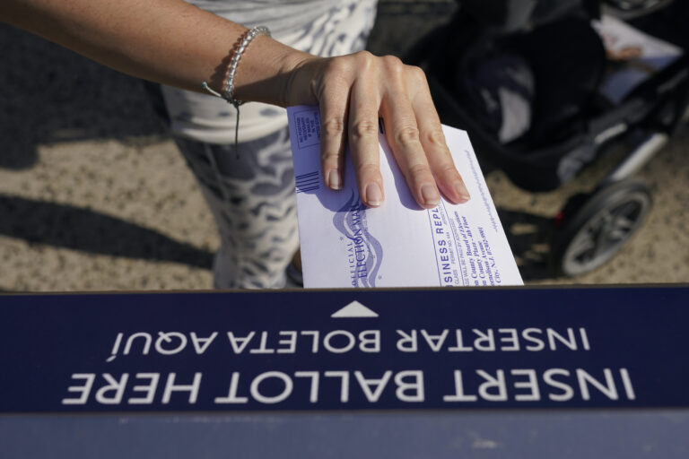 A woman deposits her ballot in an election drop box in Jersey City, N.J.