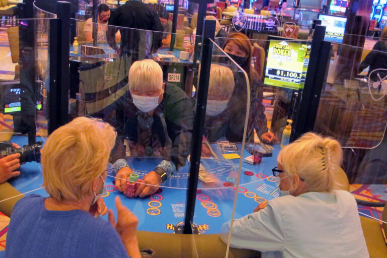 See-through barriers separate gamblers and a dealer at a card table at the Hard Rock casino