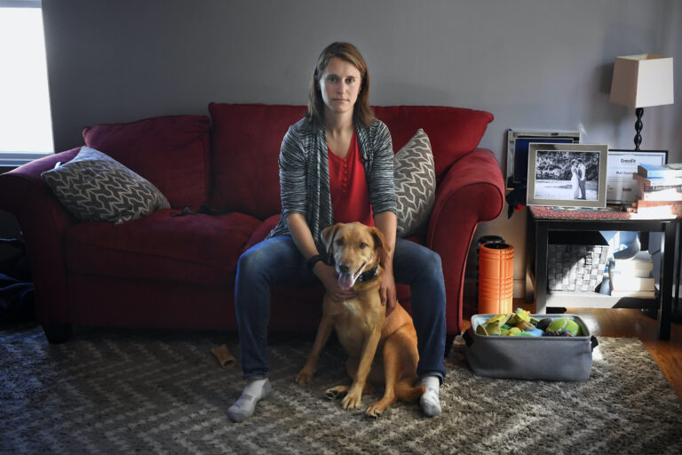 Melissa Wilhelm Szymanski sits with her dog Cooper at home in Glastonbury, Conn.