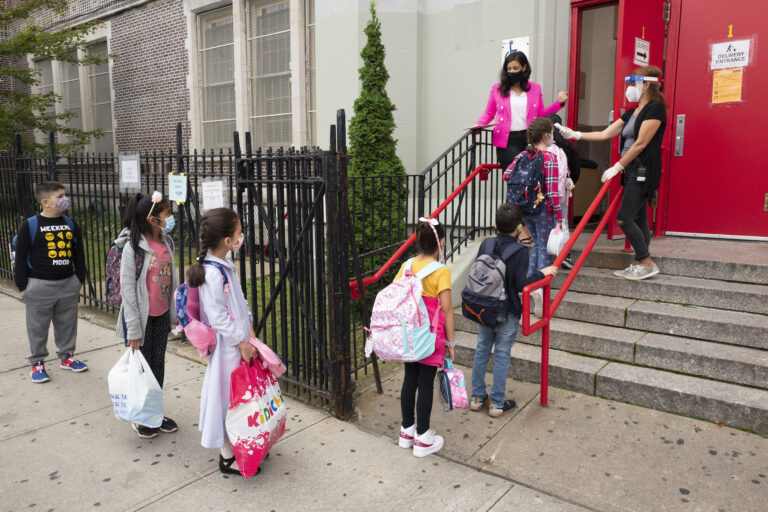 Students line up to have their temperature checked before entering PS 179 elementary school