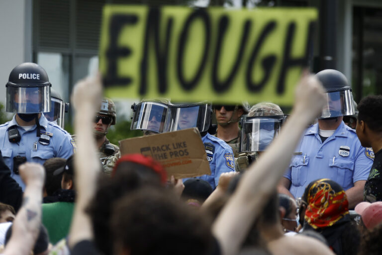 Protesters rally as Philadelphia Police officers and Pennsylvania National Guard soldiers look on in Philadelphia