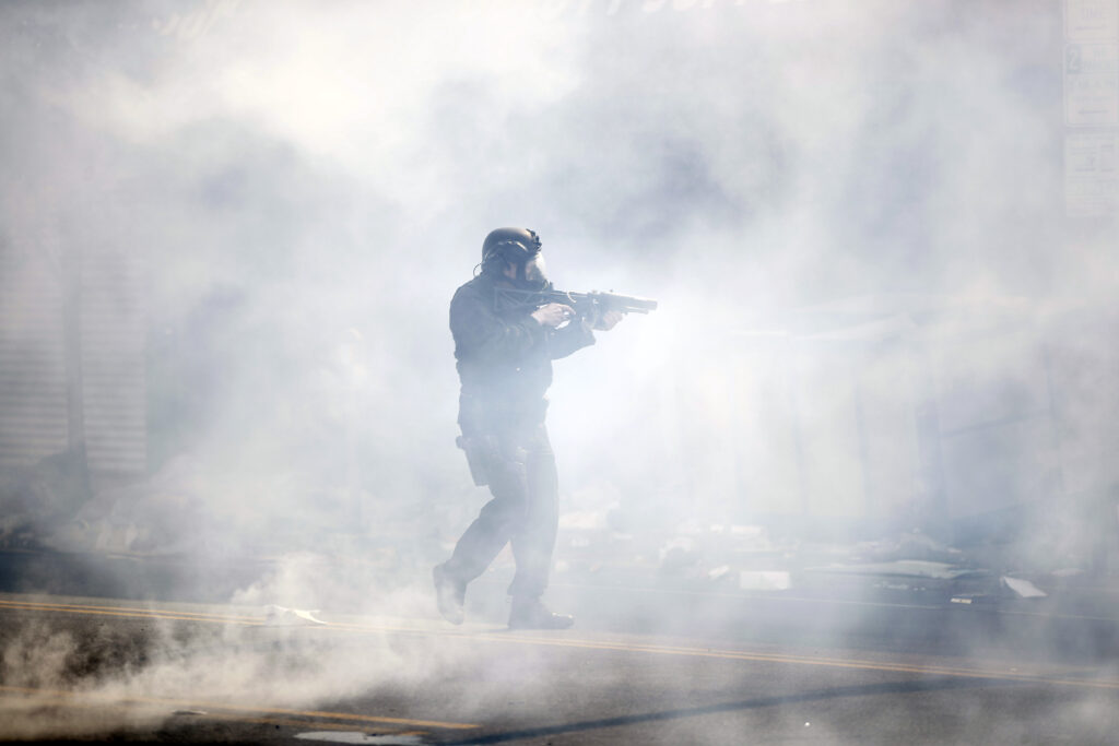 A police officer moves through tear gas deployed to disperse a crowd as Justice for George Floyd Philadelphia protests continue in Philly