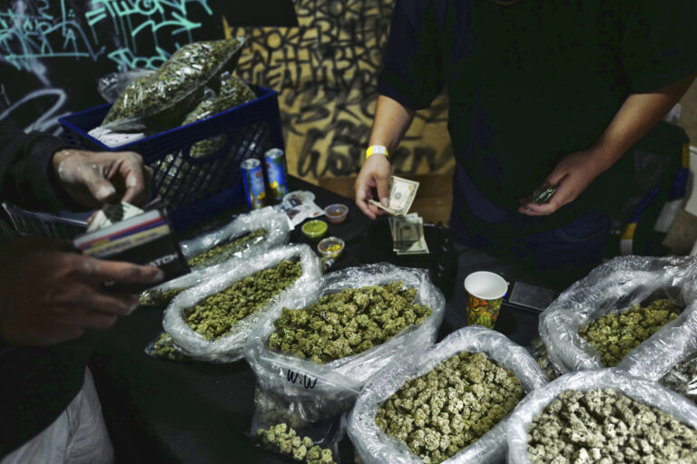 A vendor makes change for a marijuana customer at a cannabis marketplace
