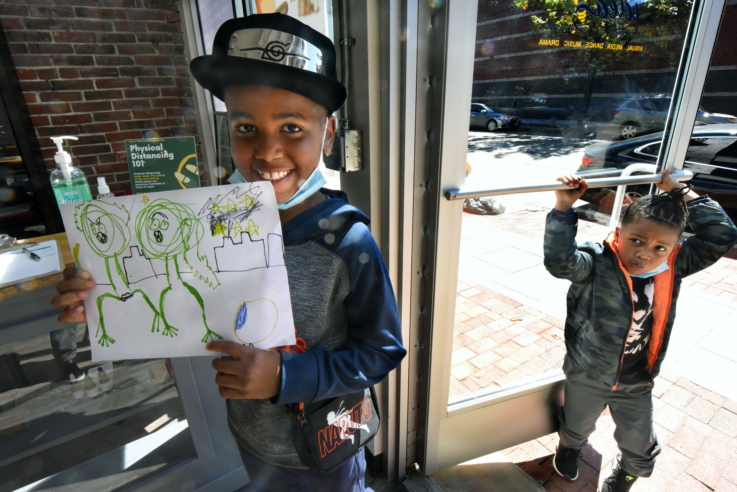 Efun Deji, 8, shows a drawing he made in his first art class