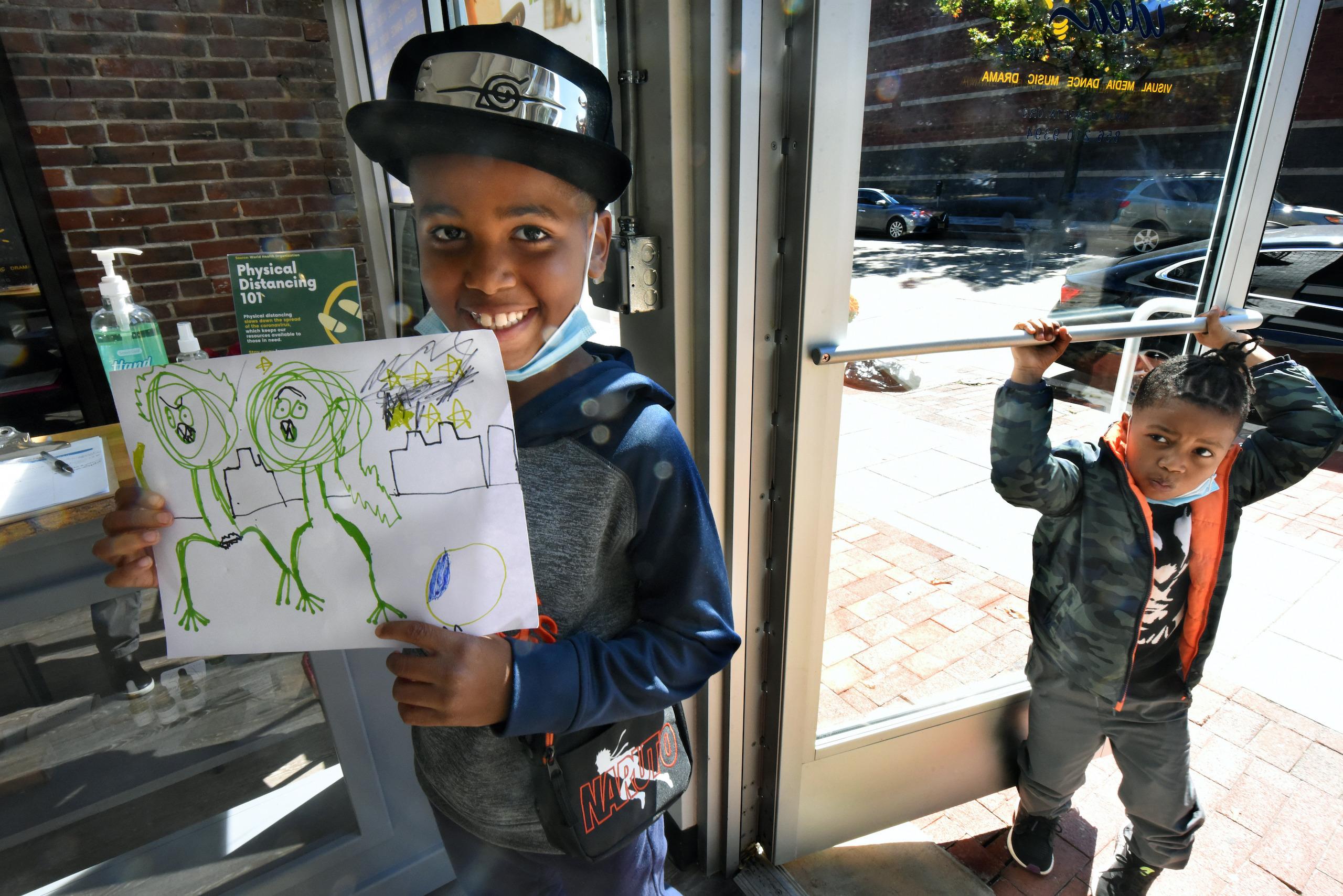 Efun Deji, 8, shows a drawing he made in his first art class
