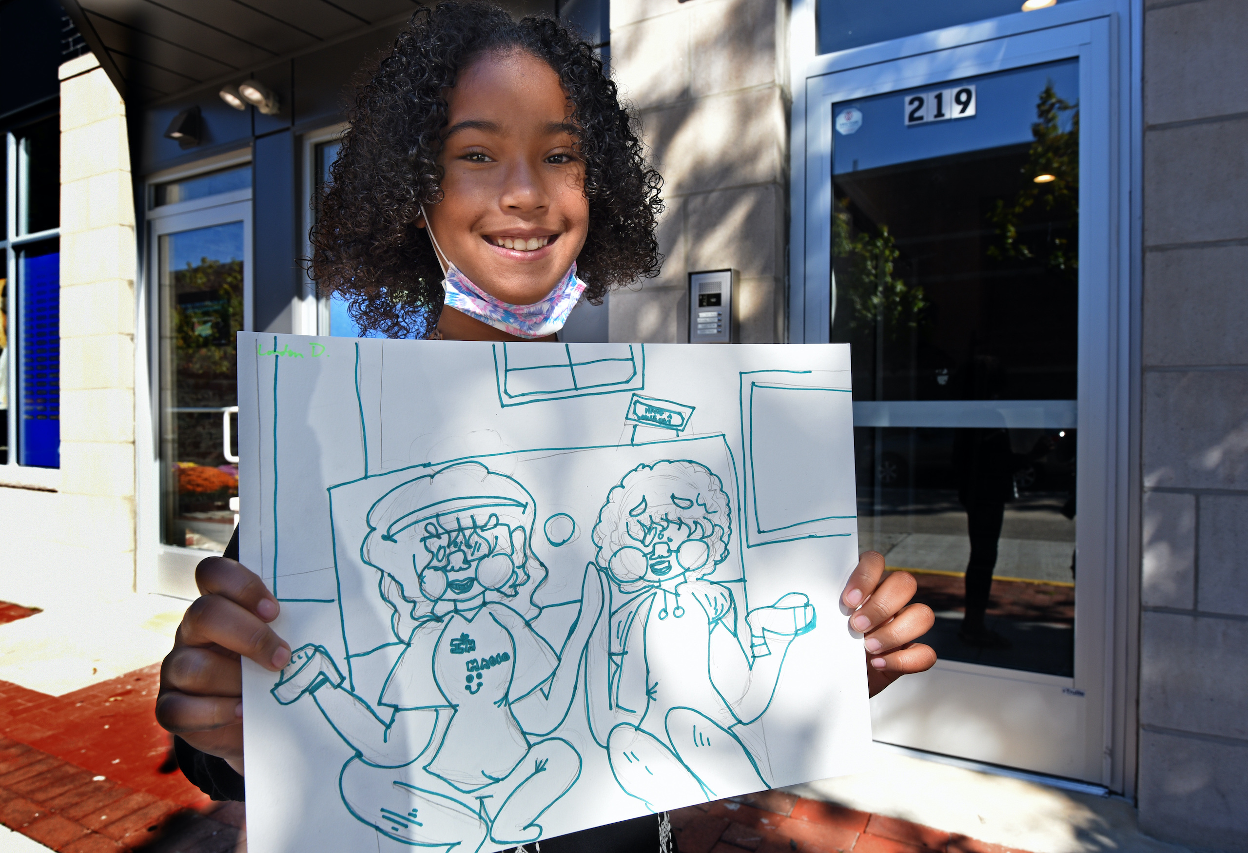 "Art student London Daniels, 10, shows a drawing she made with the theme ""togetherness."""