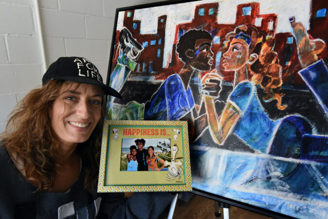 Art teacher Marcy Morris poses with a photograph of her own children and one of her works named