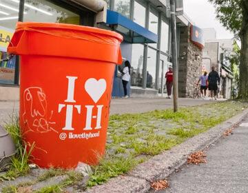 I Love Thy Hood branded trash can on a sidewalk