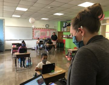 Jordan Collings teaches her EastSide Charter third-graders who are in the classroom as well as at home. (Cris Barrish/WHYY)
