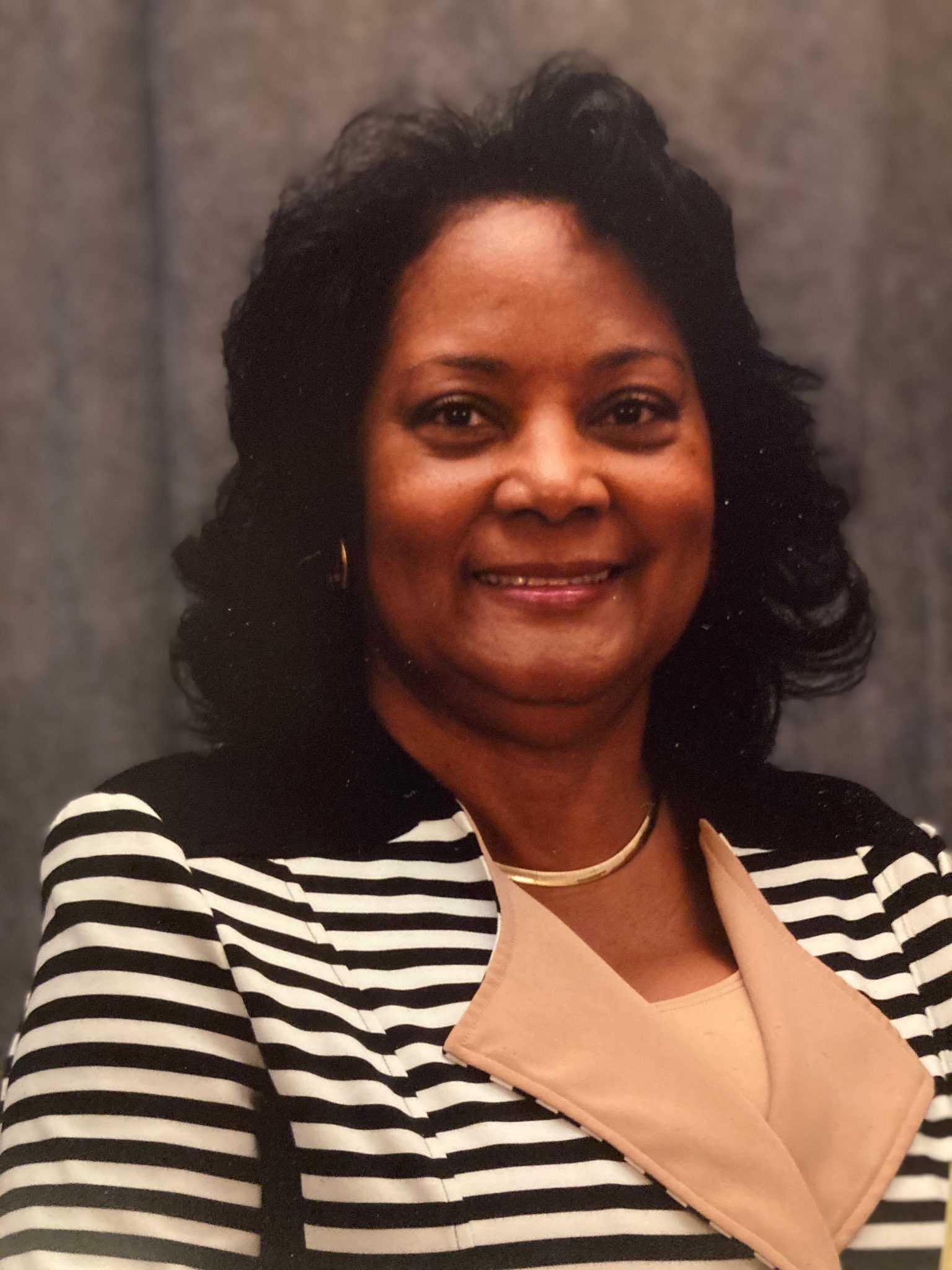 Dr. Pamela Huffman-DeVaughn, a Black woman, wearing a black-and-white striped blazer.