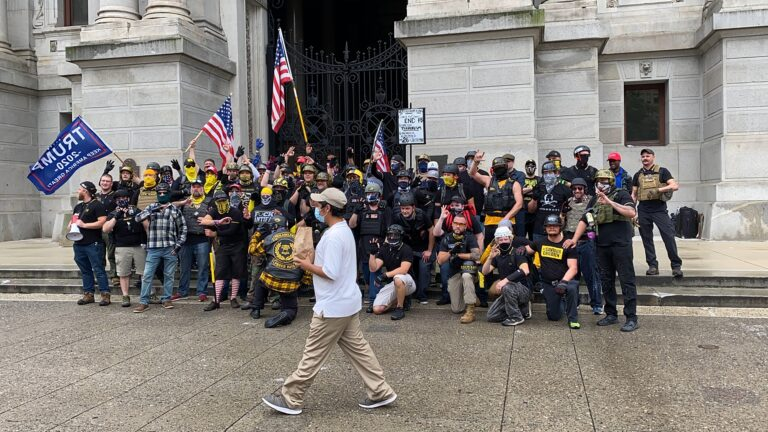 Passerby walks between the camera and the Proud Boys as they pose for a photo. (Courtesy of Jason Peters)