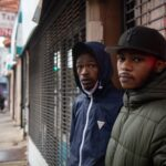 Two young Black men standing in front of a storefront.