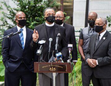 Reverend Robert Collier, president of the Philadelphia Black Clergy (center), speaks at a press conferencw