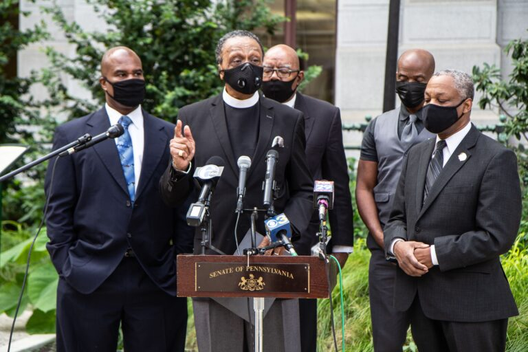 Reverend Robert Collier, president of the Philadelphia Black Clergy (center), speaks at a press conferencw