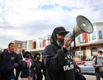 Community activist Isaac Gardner leads a march on Locust Street demanding justice for Walter Wallace Jr., who was shot dead by police Monday. (Emma Lee/WHYY)