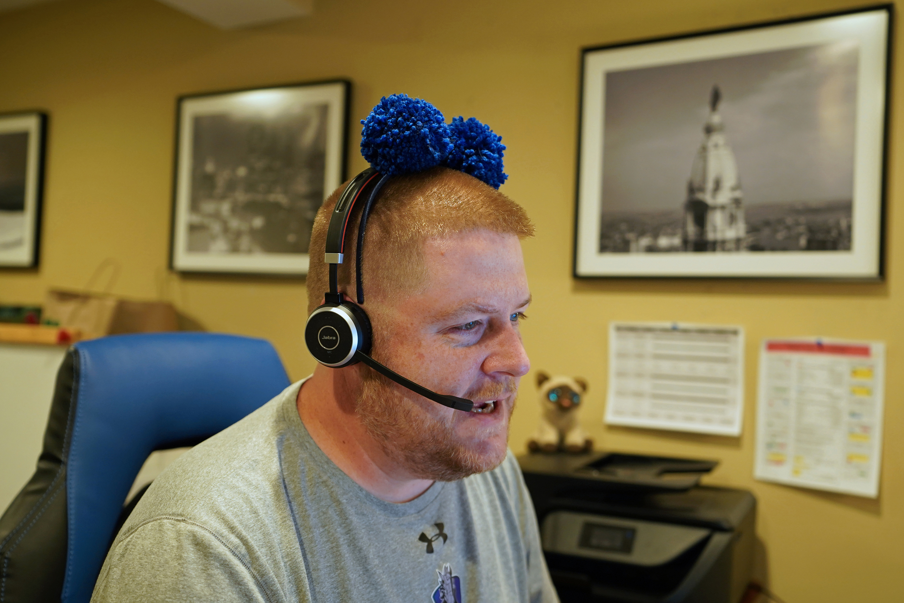 Kyle Wilson wears a headband he sometimes uses for levity with students as he works at his desk