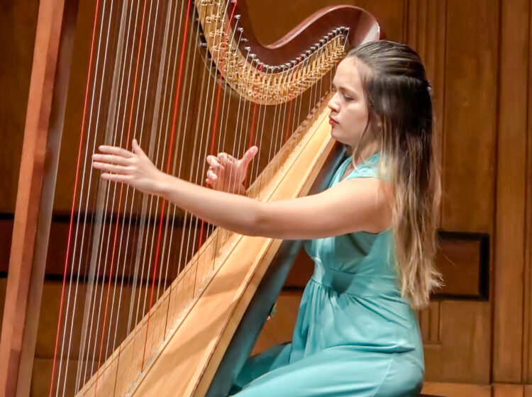 Claire Thai wearing a teal dress playing the harp on stage