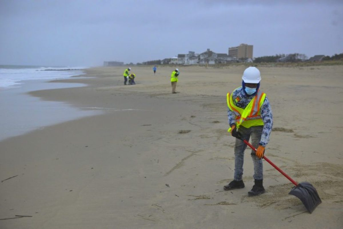 Workers help clean Delaware beach after oil spill
