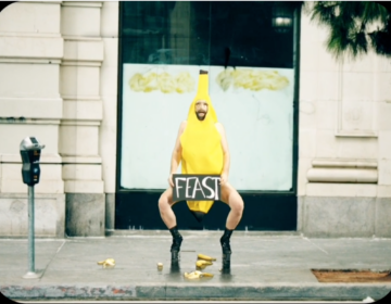 A person in a banana costume holding a sign that says
