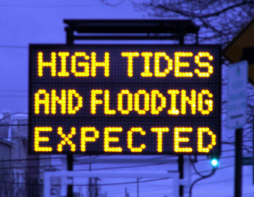 A road sign warns of high tides and expected flooding