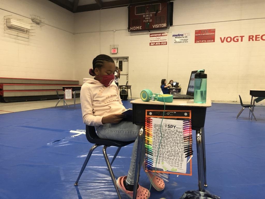 Faith Allen, 10, reads at her desk in Vogt Access Center gymnasium