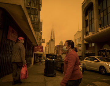 People wearing protective masks walk on Stockton Street in the Chinatown district of San Francisco