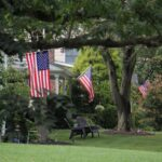 Flags fly from suburban homes in Moorestown, N.J.. (Emma Lee/WHYY)