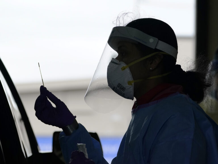 A University of Washington research coordinator holds up a swab after testing a someone for coronavirus on Oct. 23 in Seattle. (Elaine Thompson/AP Photo)