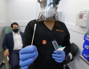 A medical assistant holds a swab after testing a man on Wednesday at the new COVID-19 testing facility at Boston Logan International Airport. (Elise Amendola/AP Photo)