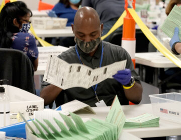 Election workers sort ballots at the Maricopa County Recorder's Office in Phoenix. Mail-in ballots in Arizona are already being counted. (Matt York/AP Photo)
