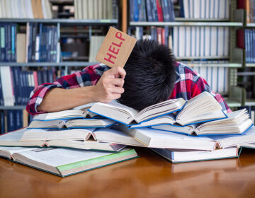 A tired and stressed student with his head down on a pile of books holding up a
