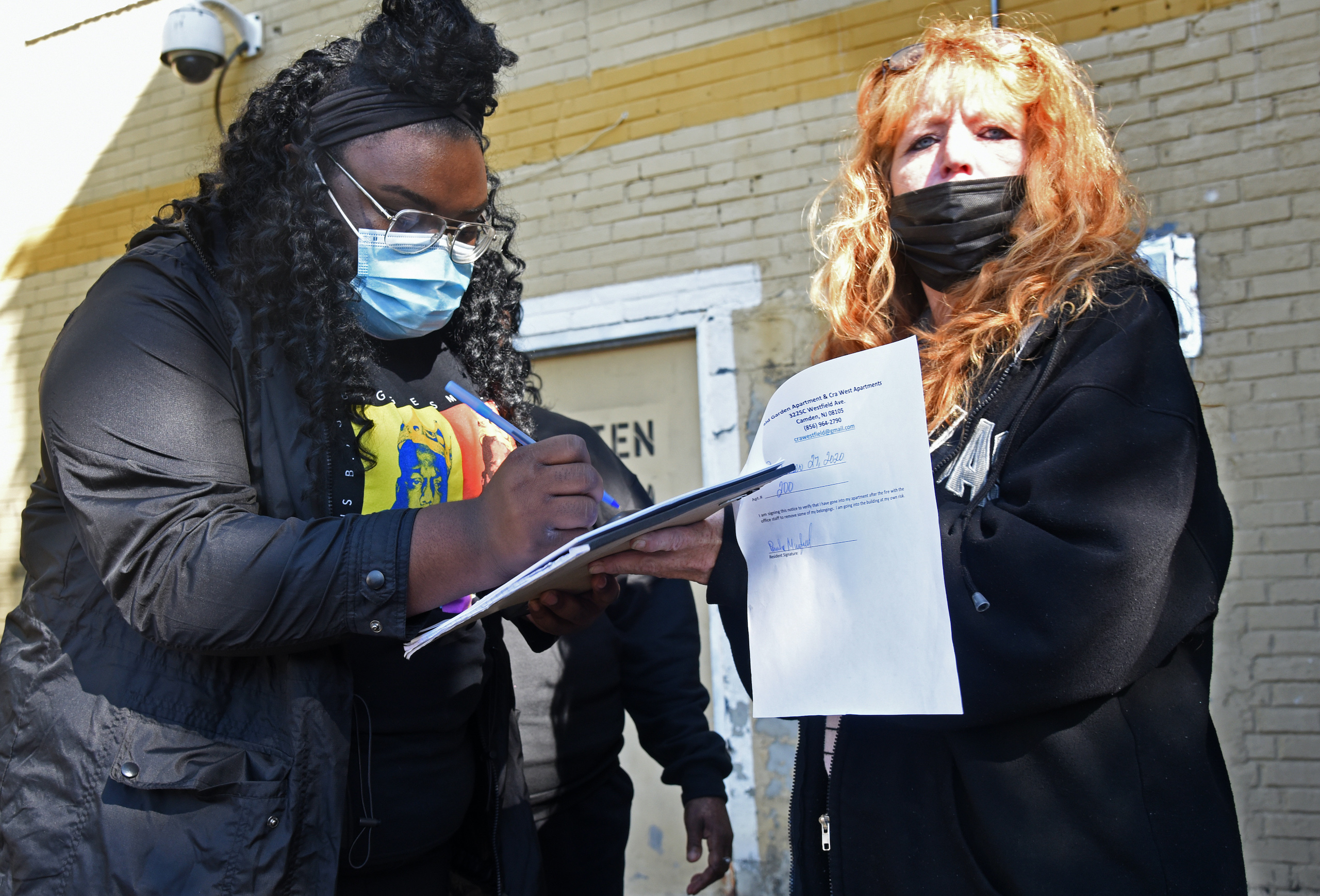 Renant Jessica Lynn signs a document allowing her to retrieve belongings from the apartment she shared with her mother; at right is property manager Gidget Bower