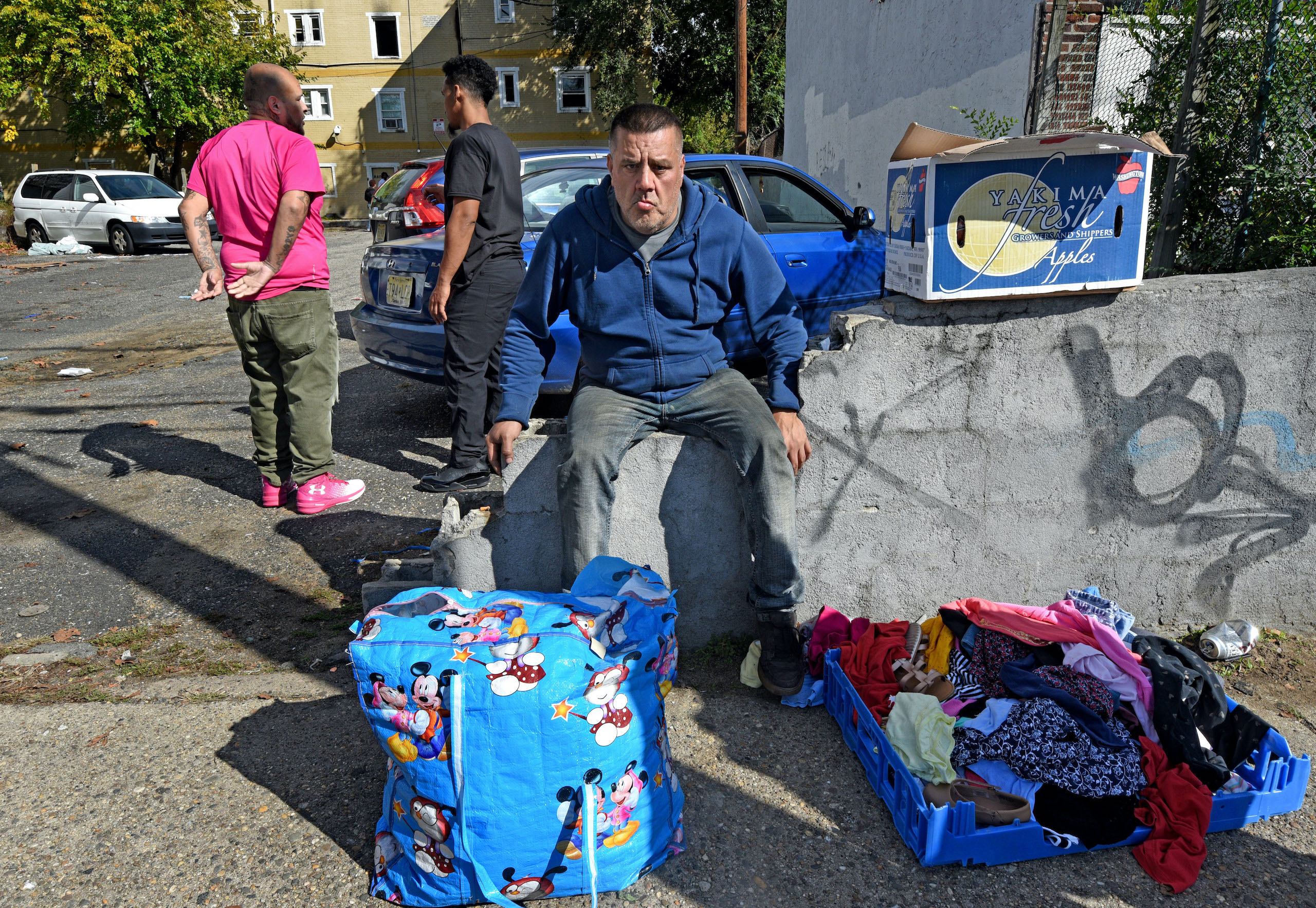 Samuel Velez sits with his belongings in the wake of the fire