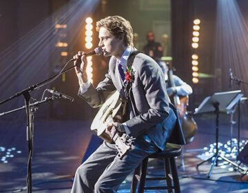Actor Fin Argus on stage with a guitar singing as Zach Sobiech in the movie Clouds