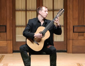 John Marcel Williams performing classical guitar on stage