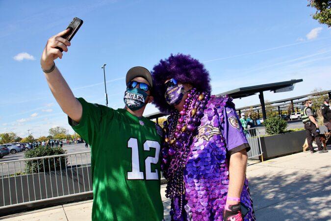 Eagles fan Mike Harbeson stops to take a selfie with elaborately costumed Ravens fan Ken Mioduski