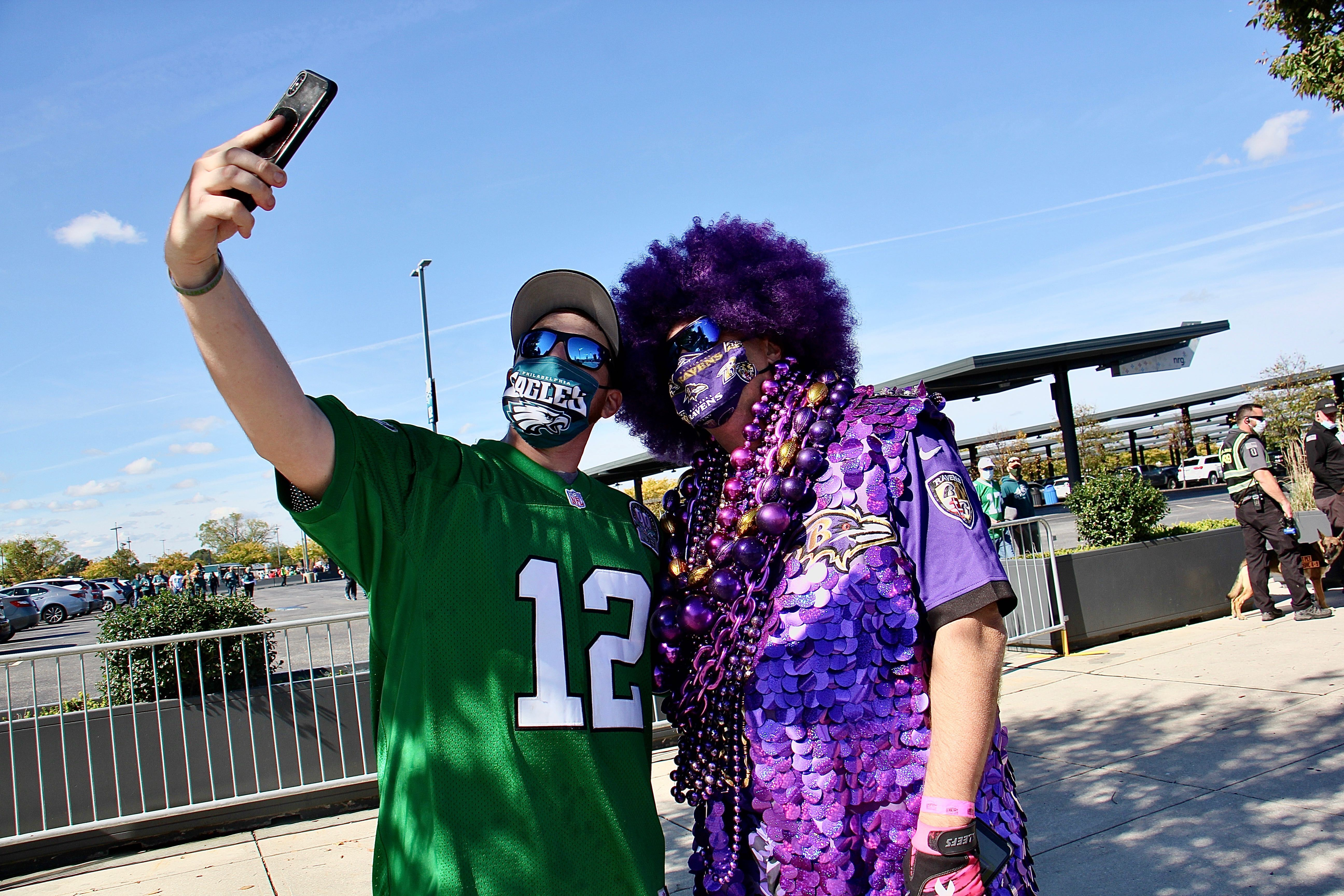 Eagles fan Mike Harbeson stops to take a selfie with elaborately costumed Ravens fan Ken Mioduski
