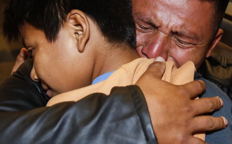 David Xol of Guatemala hugs his son Byron