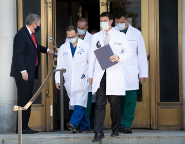 White House chief of staff Mark Meadows holds the door for Dr. Sean Conley and other members of the president's medical team on Sunday. Another update on Trump's condition is expected sometime on Monday.