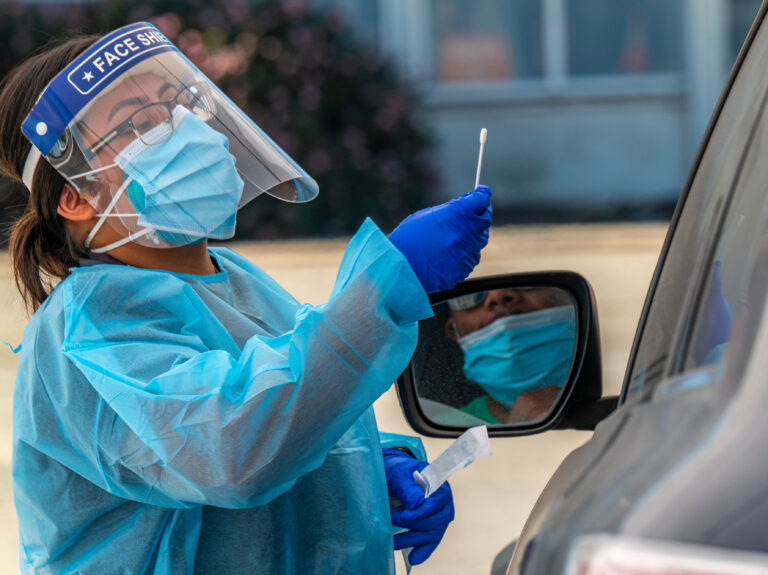 A medical worker in PPE administers a rapid COVID-19 test.