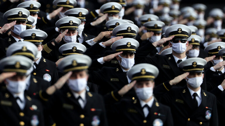Midshipmen wearing face masks stand and salute.