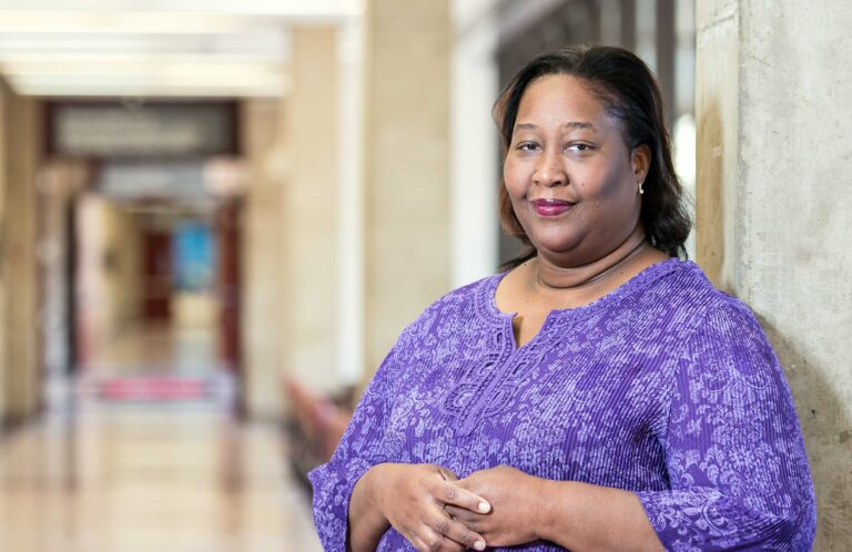 Dr. Damali Campbell-Oparaji, a Black woman, wearing a purple shirt stands in a hallway.