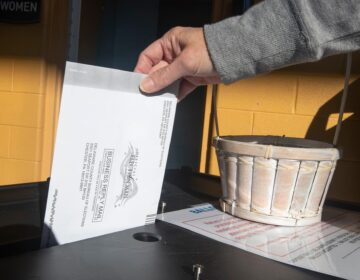 A voter returns their mail ballot
