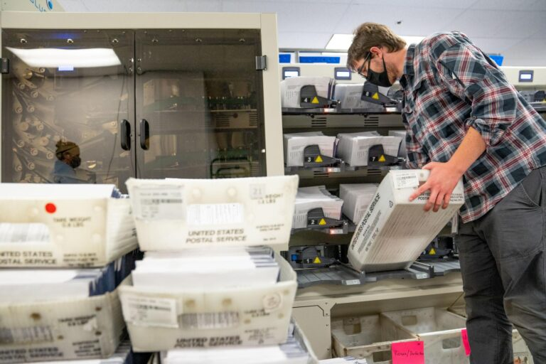 An elections worker organizes mail ballots in Chester County